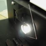 Transparent plastic plaque beaing measured for color and haze in TTRAN transmission on a HunterLab sphere instrument.